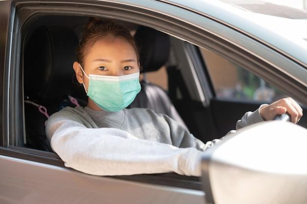 車に座っているマスクの美しい少女、