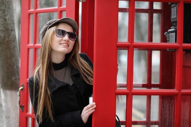 電話ブースの美しい少女。女の子は公衆電話から電話で話している。通りにある英語の電話ブースと電話で話している女性。