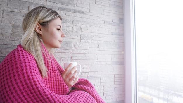 一杯のコーヒーとピンクの格子縞の美しい少女。バルコニーの若い女性。居心地の良い朝食のために一杯のコーヒーのために休んでください。