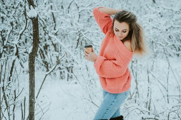 Красивая молодая девушка в розовом объемном свитере и джинсах с кофе в руках в холодном снежном зимнем лесу