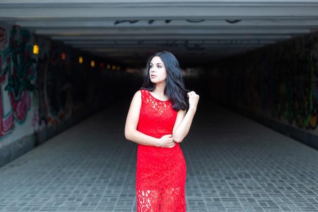 街の地下交差点を背景に赤いドレスを着た美しい少女。