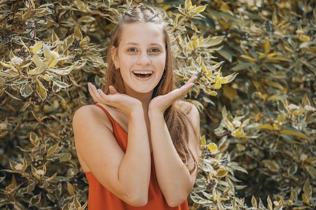 葉の背景に赤いドレスを着た美しい少女。