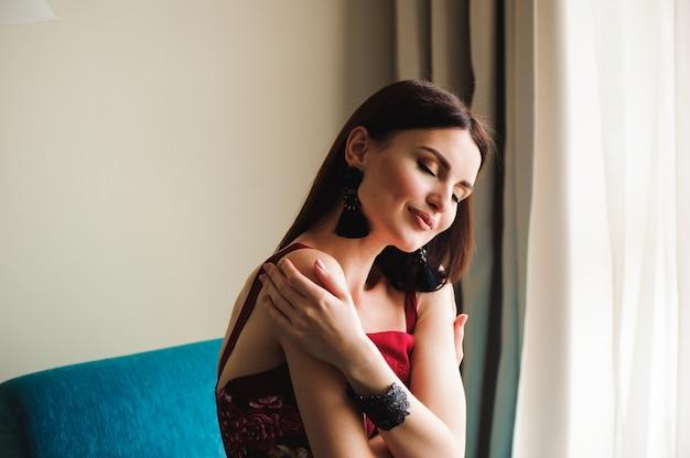 창이에 앉아 빨간 드레스를 입고 아름 다운 소녀