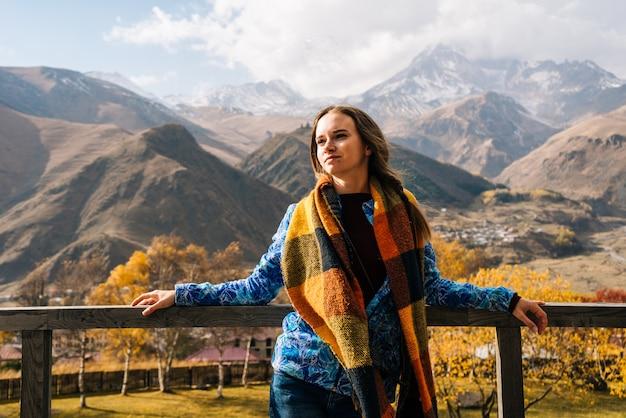 暖かいジャケットを着た美しい少女が旅行し、高山の中に立って、自然を楽しんでいます