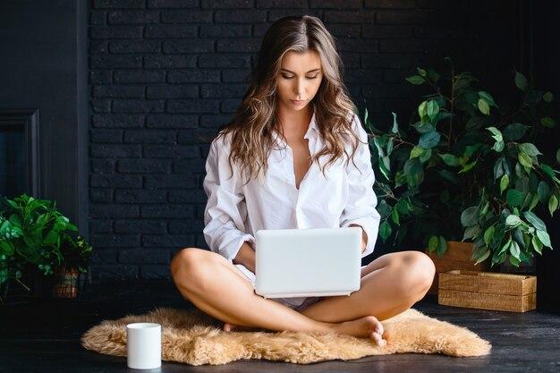 Красивая молодая девушка в рубашке белого человека, используя ноутбук, сидя на ковре