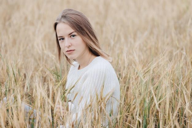 白いセーターの美しい少女は麦畑に座って、カメラを思慮深く見てください。
