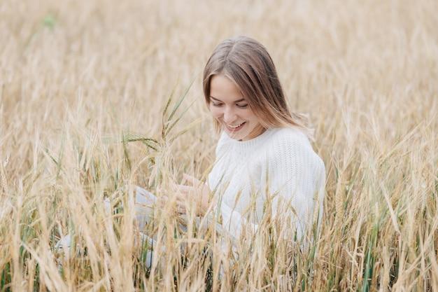 白いセーターの美しい少女は麦畑に座って、元気に笑顔します。