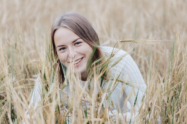 麦畑と笑顔で白いセーターの美しい少女が座っています。