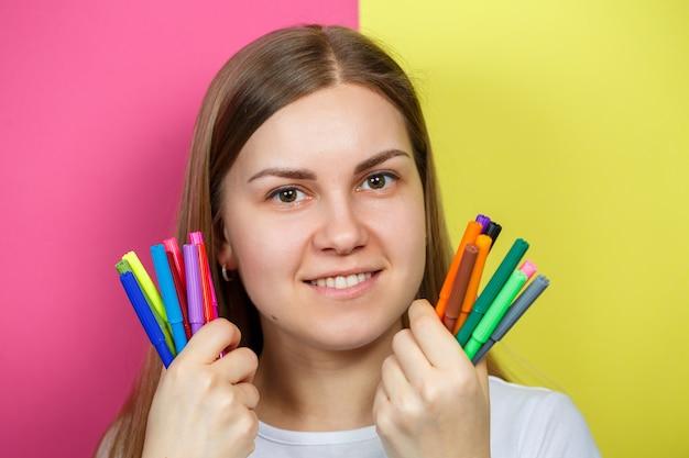 Красивая молодая девушка в белой футболке держит разноцветные фломастеры для рисования