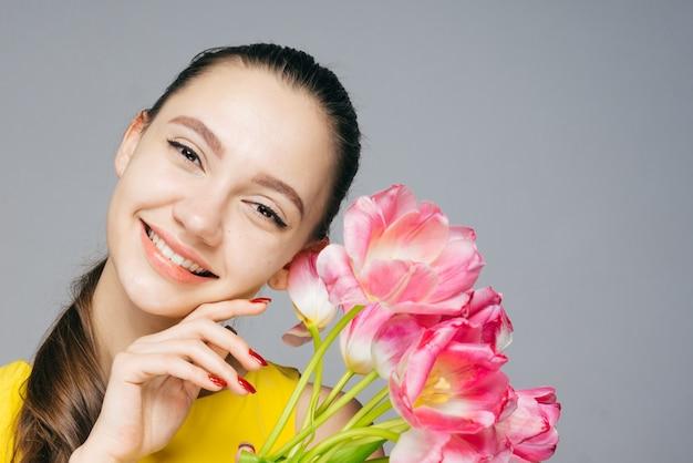 노란 드레스를 입은 아름다운 소녀는 미소를 짓고 향기로운 봄 꽃 꽃다발을 들고 있습니다