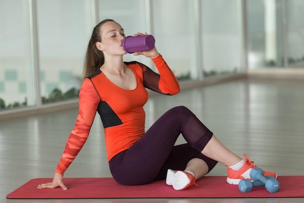 明るいスポーツスーツの美しい少女は、トレーニング中に空のジムでダンベルの横にある敷物の上に座っているボトルから水を飲みます