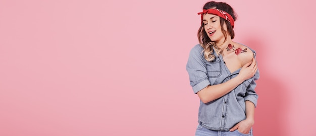 Красивая молодая девушка в джинсовой рубашке с наклейкой воды татуировки цветов наклейки и улыбается на розовом фоне
