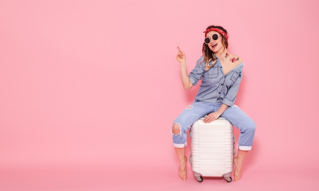 Красивая молодая девушка в джинсовой рубашке с наклейкой татуировки воды наклейка цветы, улыбаясь и сидя на чемодане