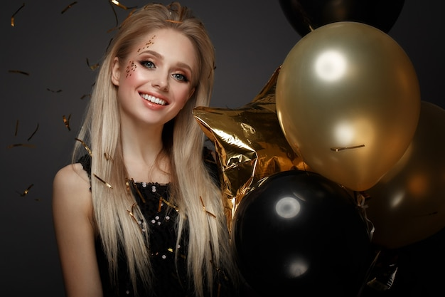 お祝いの風船とエレガントなイブニングドレスの美しい少女。美顔。スタジオで撮影した写真