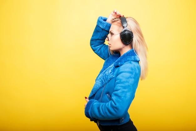 Красивая молодая девушка в модных солнцезащитных очках с наушниками в синем модном пальто на желтом