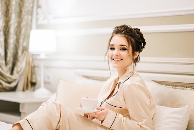Красивая молодая девушка в золотой пижаме в роскошной комнате со стильными волосами и макияж, лежа в постели с чашкой кофе. утренняя невеста.
