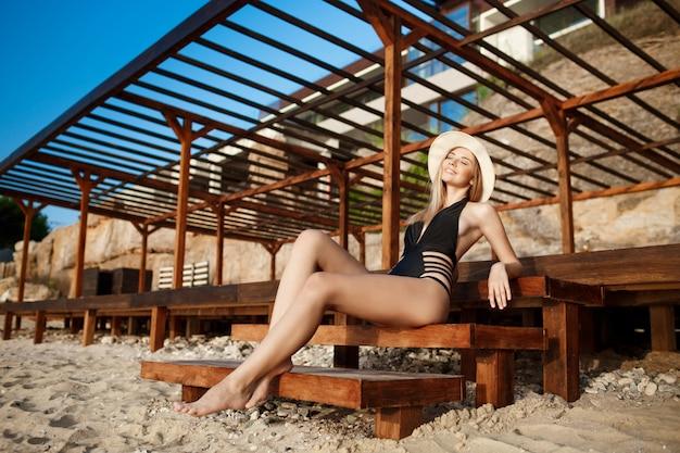 Красивая молодая девушка в шляпе лежит на утреннем пляже