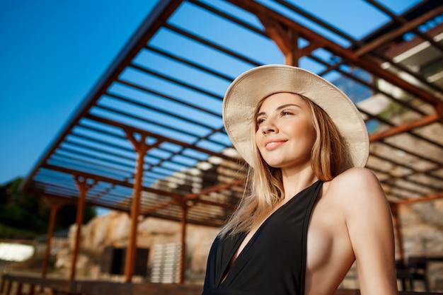朝のビーチでかかっている帽子の美しい少女