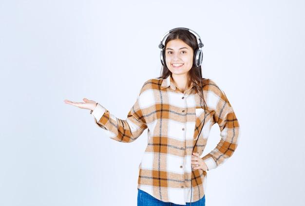 白い壁の上の歌を聞いているヘッドフォンの美しい少女。