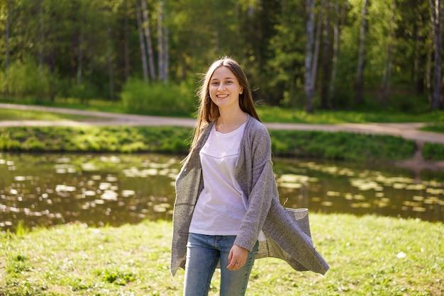 ジーンズと白いtシャツの美しい少女が湖の近くを歩く
