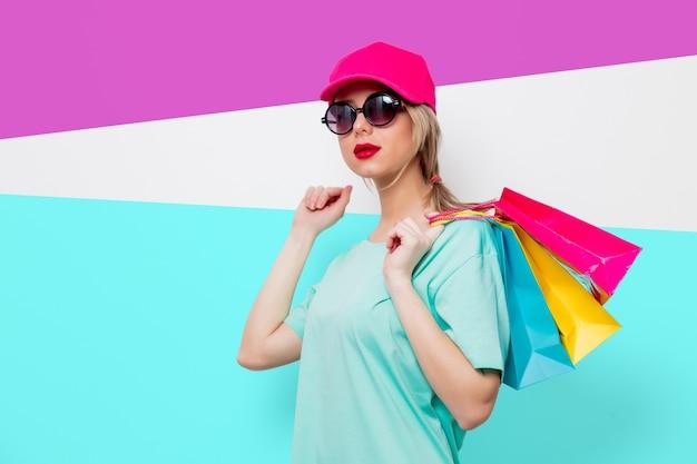 분홍색 모자와 쇼핑백 onpurple 및 파란색 배경으로 파란색 티셔츠에 아름 다운 젊은 여자.