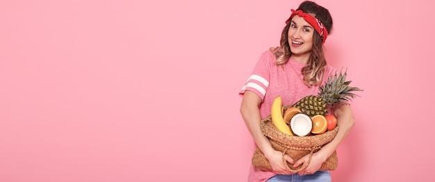 Красивая молодая девушка в розовой футболке, держит полную соломенную сумку с фруктами на розовой стене