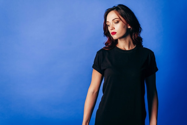 青のスタジオで黒のtシャツでポーズをとって美しい少女
