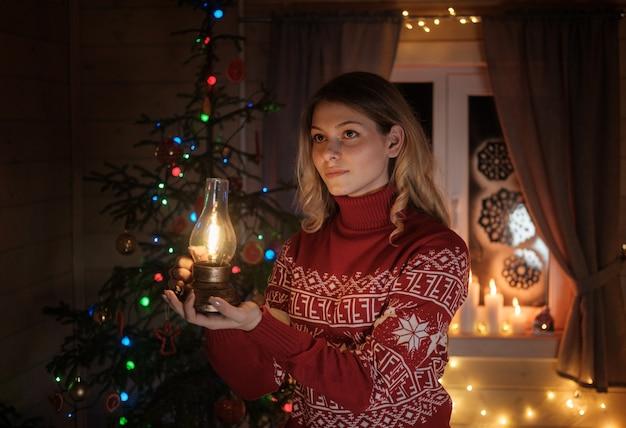 크리스마스 나무에 빨간 스웨터에 아름 다운 젊은 여자. 축제 인테리어, 양초, 조명, 화환. 크리스마스 밤에 여자의 초상화
