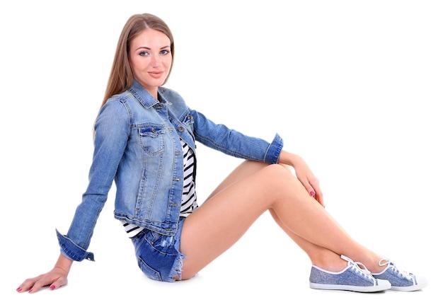 Красивая молодая девушка в шортах, куртке и футболке на белом