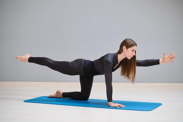 운동복을 입은 아름다운 소녀가 체조 카펫에서 운동을 하고 있다