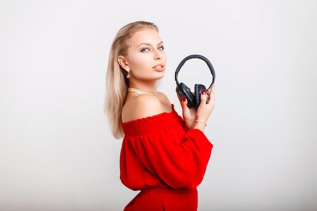 Красивая молодая девушка в стильной красной одежде держит наушники и позирует на сером