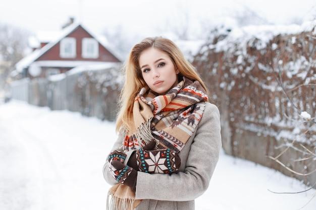 冬の日に家の近くを歩くスタイリッシュな冬の服を着た美しい少女