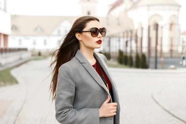 街のサングラスとコートの美しい少女