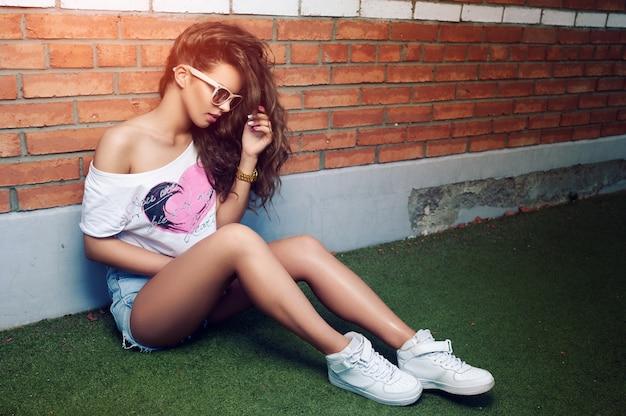 벽돌 벽의 배경에 선글라스에 아름 다운 젊은 여자. 아름다운 건강한 머리카락. 데님 반바지. 화이트 스니커즈