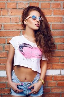벽돌 벽의 배경에 선글라스에 아름 다운 젊은 여자. 아름다운 건강한 머리카락. 데님 반바지