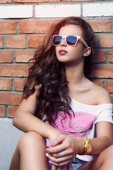 レンガの壁の背景にサングラスをかけた美しい少女。美しい健康な髪。デニムショートパンツ