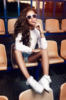 テニスコートでサングラスをかけた美しい少女。美しい健康な髪。デニムショートパンツ。白いスニーカー