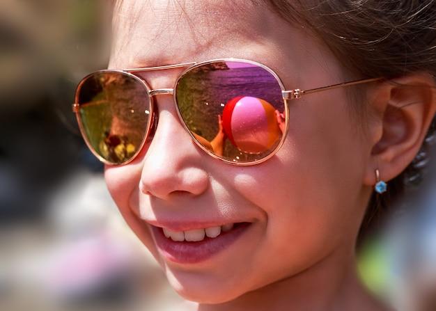 Красивая молодая девушка в солнцезащитных очках с отражением пляжного мяча