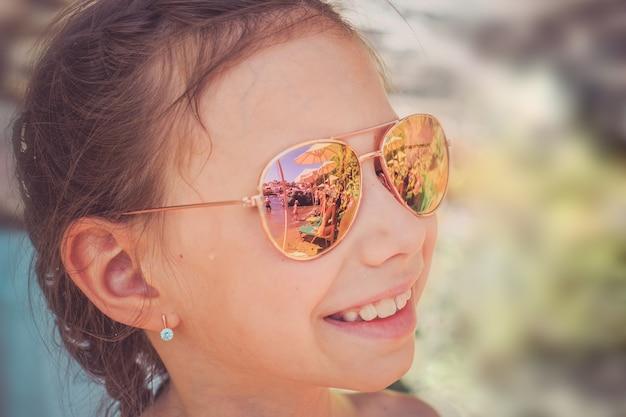 Красивая маленькая девочка в солнечных очках с отражением пляжа.