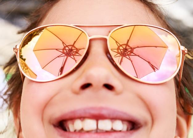 Красивая молодая девушка в солнцезащитных очках с отражением пляжного зонтика