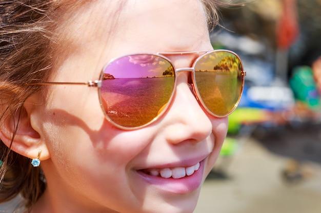 ビーチパラソル反射とサングラスの美しい少女