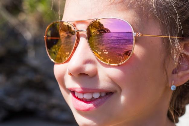Красивая молодая девушка в солнцезащитных очках с отражением моря