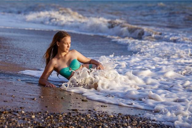 Красивая молодая девушка в купальнике на берегу в морские волны.