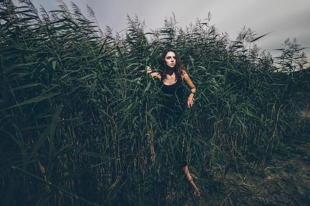 黒のドレスの草の茂みのジャングルの美しい少女