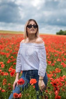 Красивая молодая девушка в маковом поле. свободное время и хорошую погоду она проводит ради удовольствия.