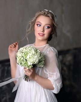 スタジオでヴィンテージのウェディングドレスで美しい少女。白い花束を持つ花嫁の肖像画。