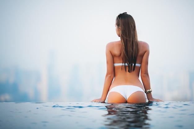 ホテルの上のプールの端に泳いで立っている白いビキニの美しい少女