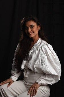 Красивая молодая девушка в белой одежде позирует в темной фотостудии. сдержанное фото. чувствительная шатенка с длинными волосами. молодая женщина с красивой улыбкой.