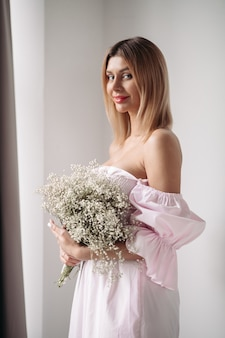 白い花のボケを保持している白いドレスの美しい少女