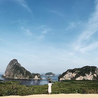 Красивая молодая девушка в белом платье смотрит на экзотические и тропические острова со скалами, синим морем и чистым голубым небом